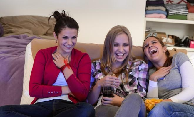 Three girls watching tv and laughing