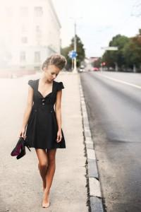 Woman wearing a little black dress walks down a road