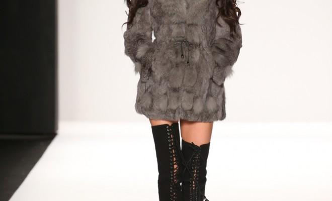 Model walks runway with lace-up thigh high boots