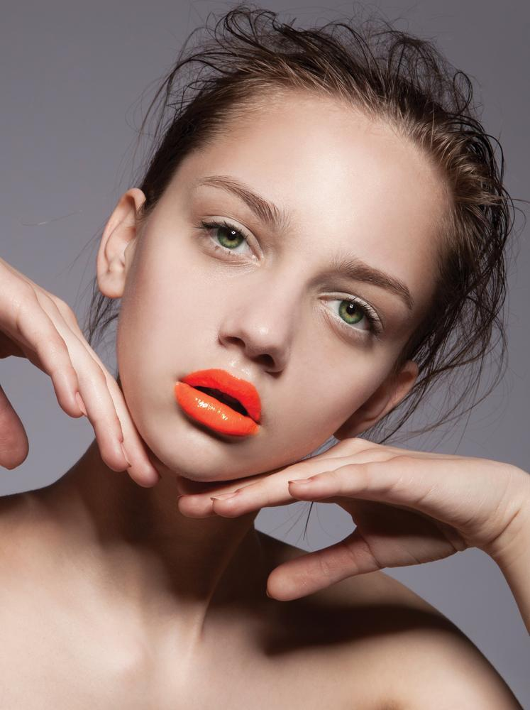 Model wears orange lipstick