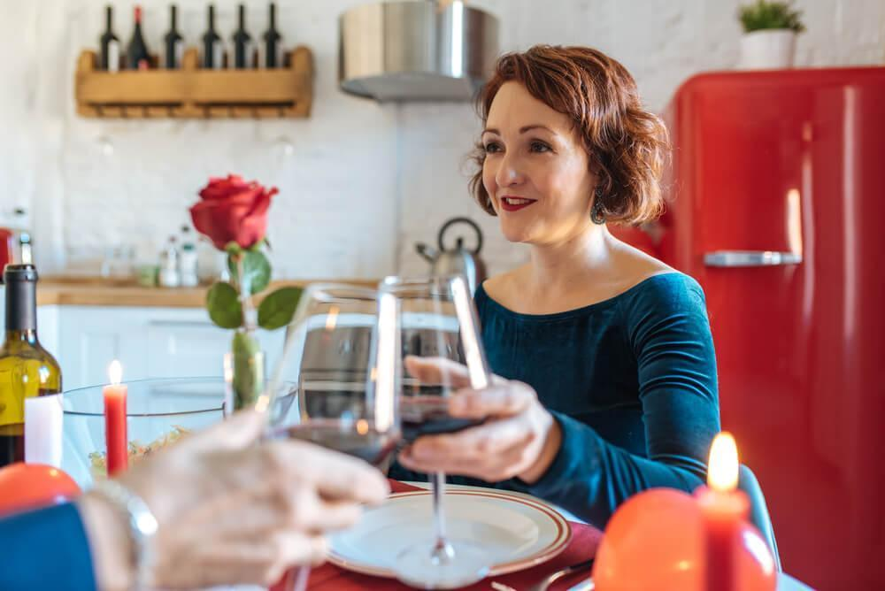 woman clinking wine glass with unseen man