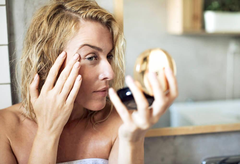 Woman examine her skin with a compact mirror