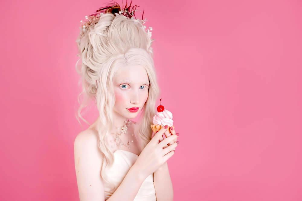 Pale woman with Marie Antoinette makeup and tall bouffant, with an ice-cream in her hand