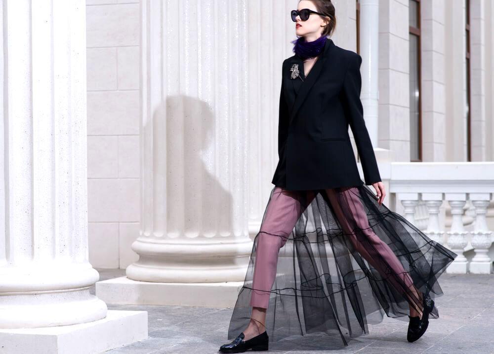 Fashionable woman in black walking near modern neo-Roman columns