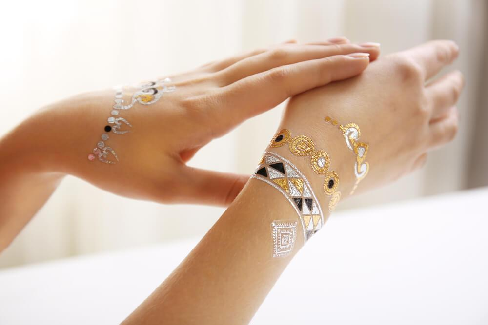 Gold and silver flash tattoos on unknown woman's wrists