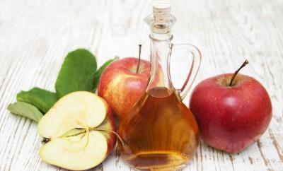 Apples and apple cider vinegar on a wood table