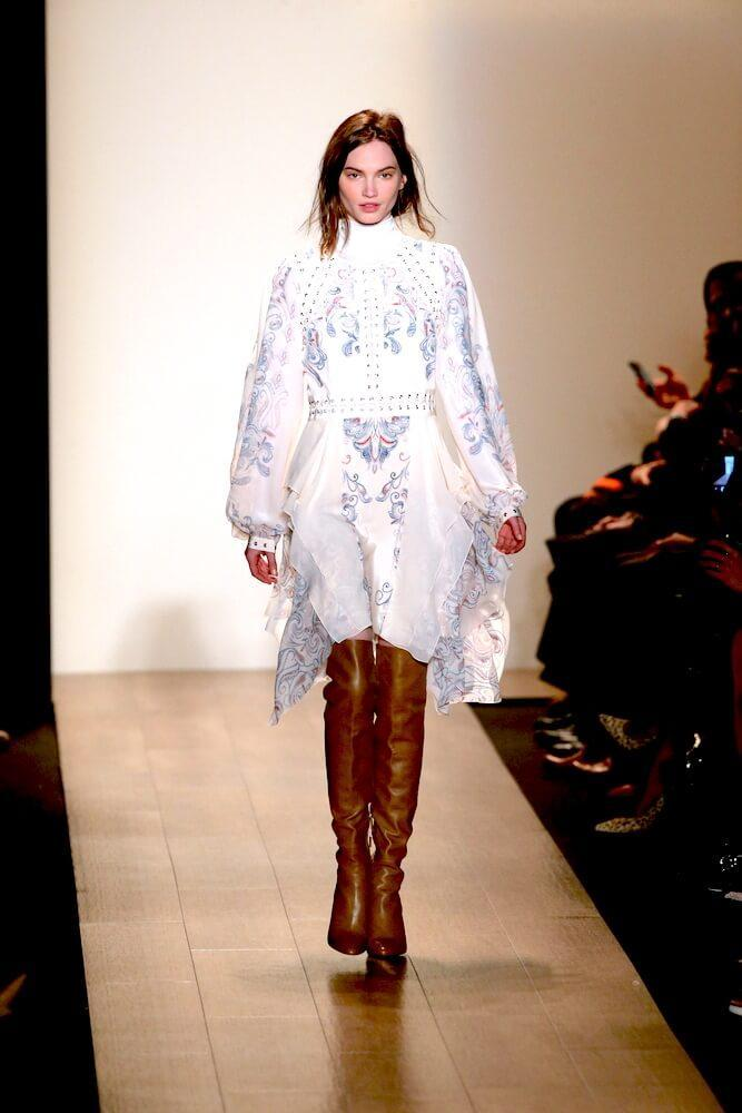 model wearing thigh high boots on the runway