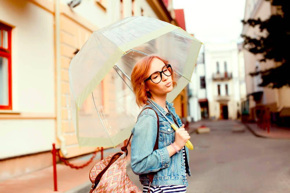 Young woman with umbrella and denim jacket outdoors