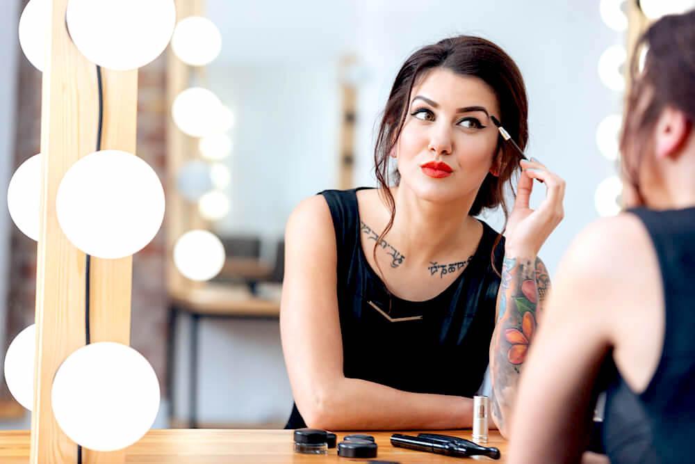 Tattooed woman applying makeup in mirror