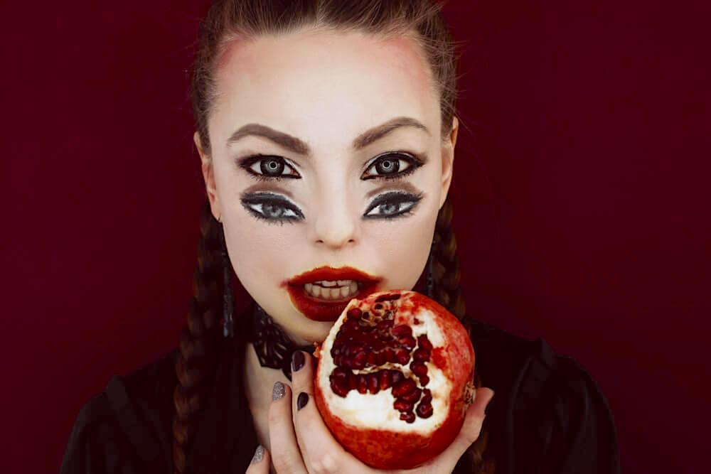 Woman with freaky four-eyes makeup and a half-eaten pomegranate