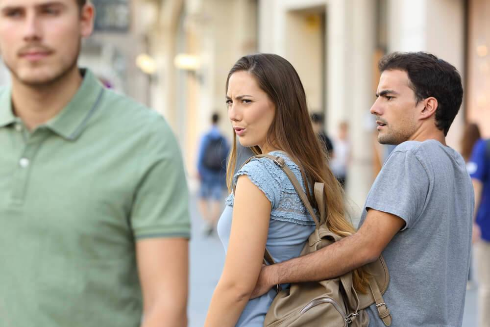 Woman looking at another man, jealous boyfriend