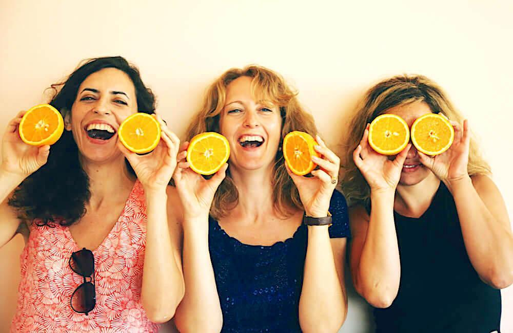 Three happy women with sliced oranges