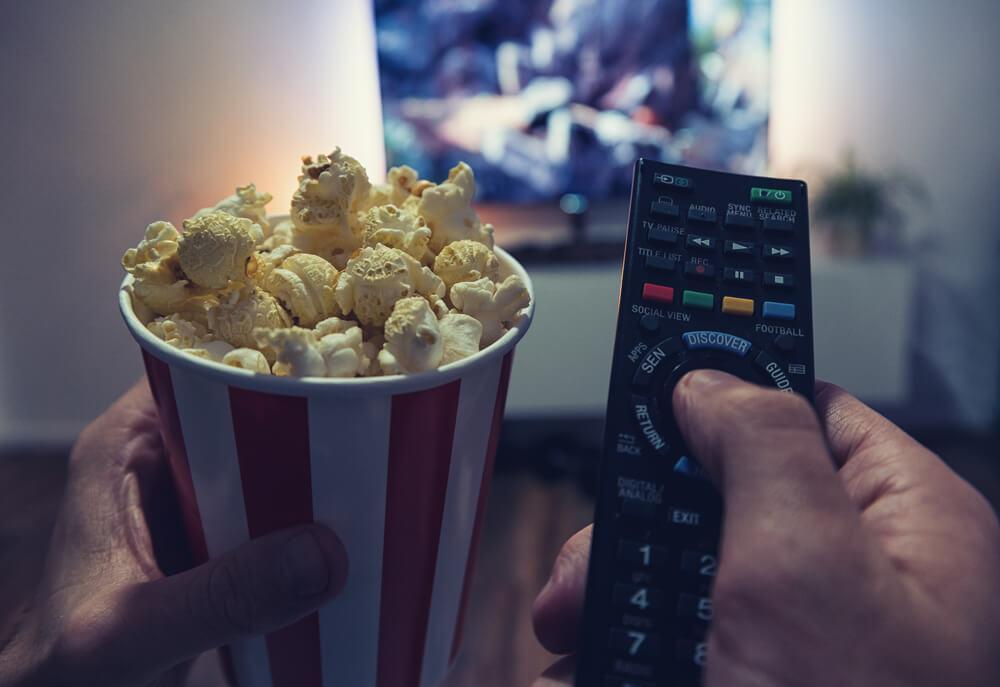 Man watching tv holding popcorn and remote