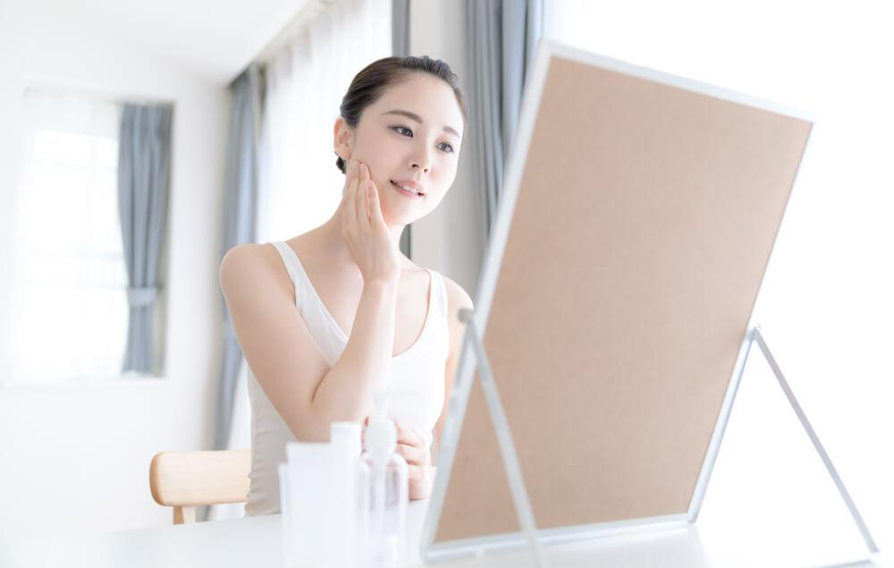 Woman in front of mirror with skin care products