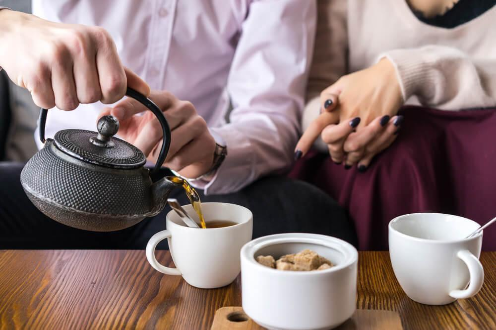 Couple pouring tea into cups