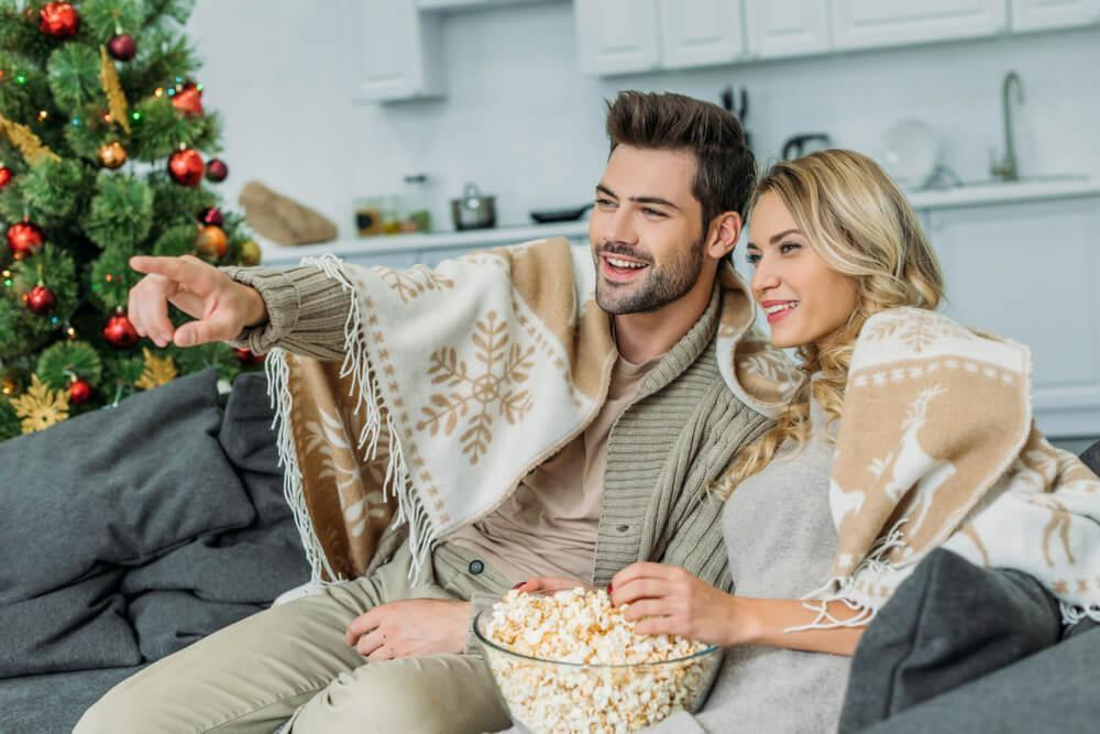Couple watching movie with popcorn and Christmas tree in background