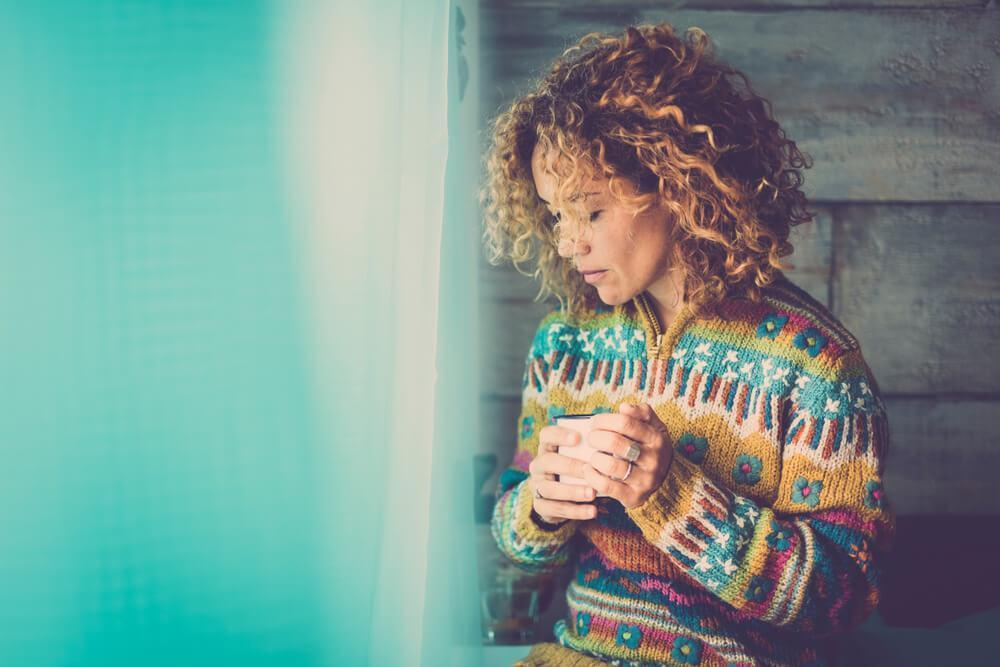 Woman standing by window looking sad