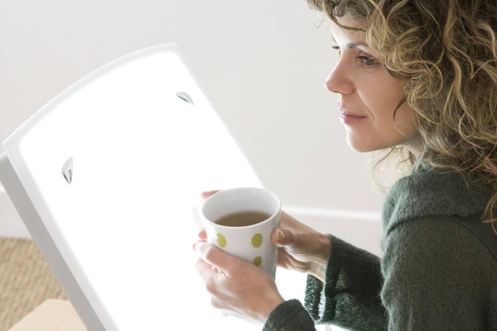 Woman using SAD light box