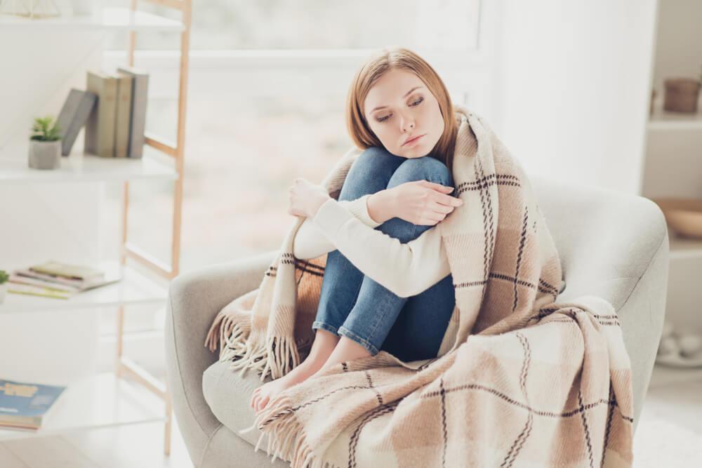 Woman hugging knees under blanket looking sad