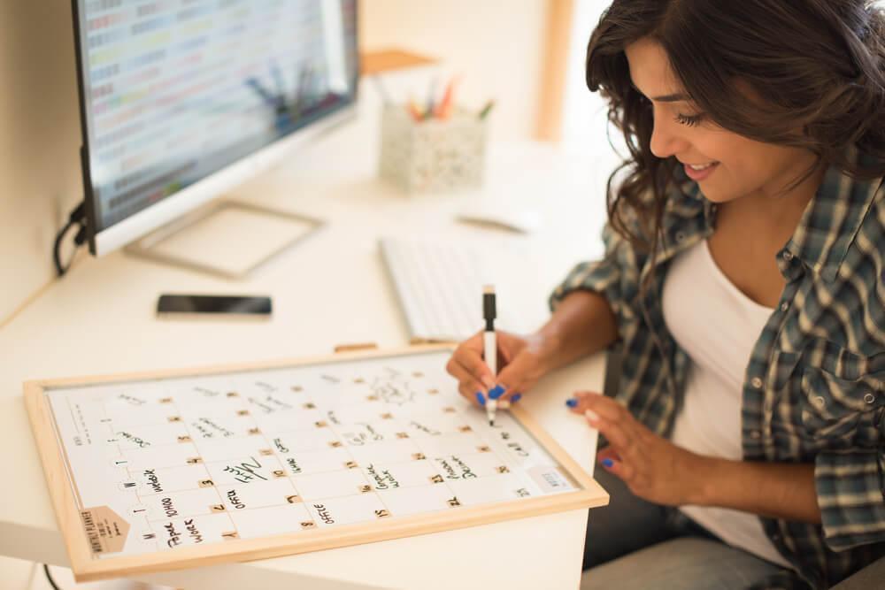 Woman writing on calendar