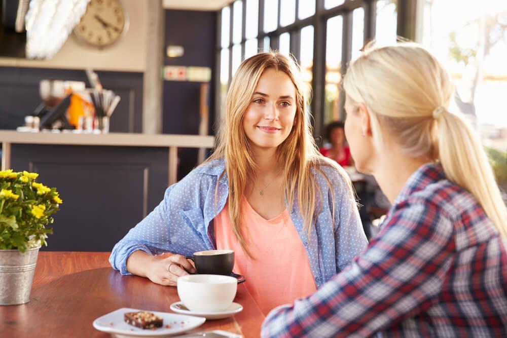 Two friends talking in cafe
