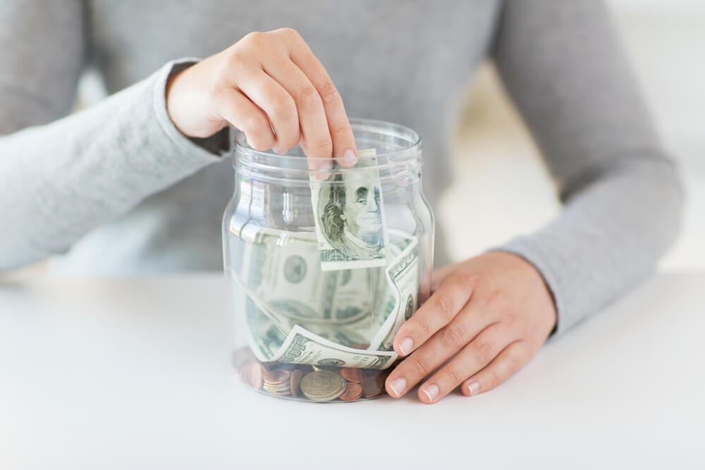 Woman placing money into a jar