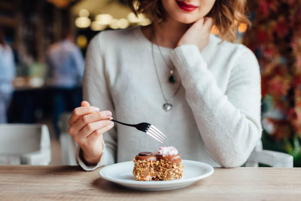 Woman at cafe eating plate of cake