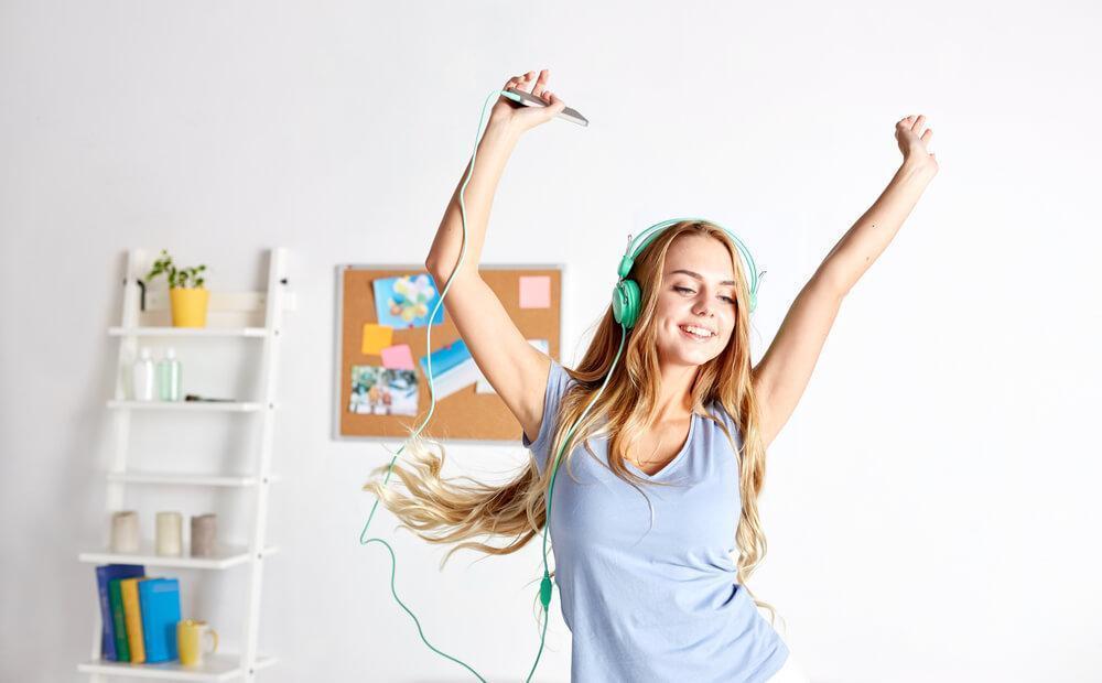 Woman dancing in bedroom with headphones on