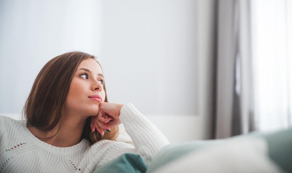 Woman on sofa thinking