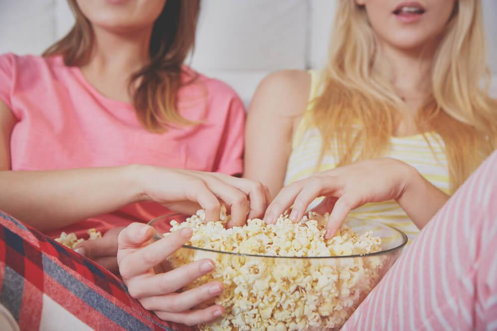 Women with hands in popcorn bowl