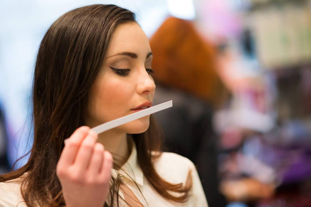 Woman sniffing perfume tester strip