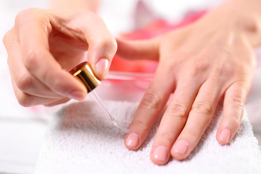 Woman using cuticle oil