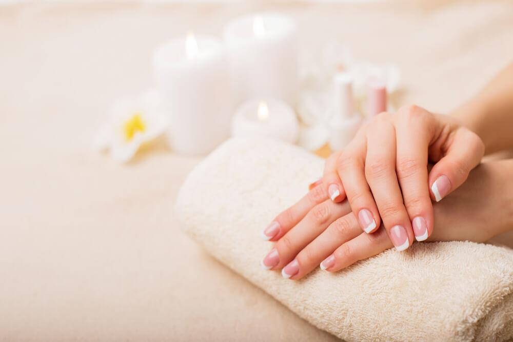 Hands with healthy nails on towel