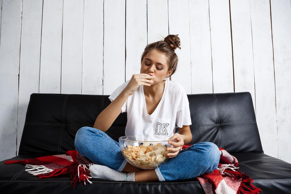Woman eating chips on sofa